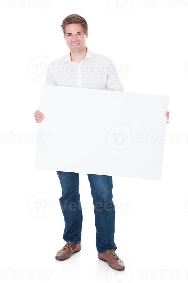 homem segurando o cartaz em branco foto