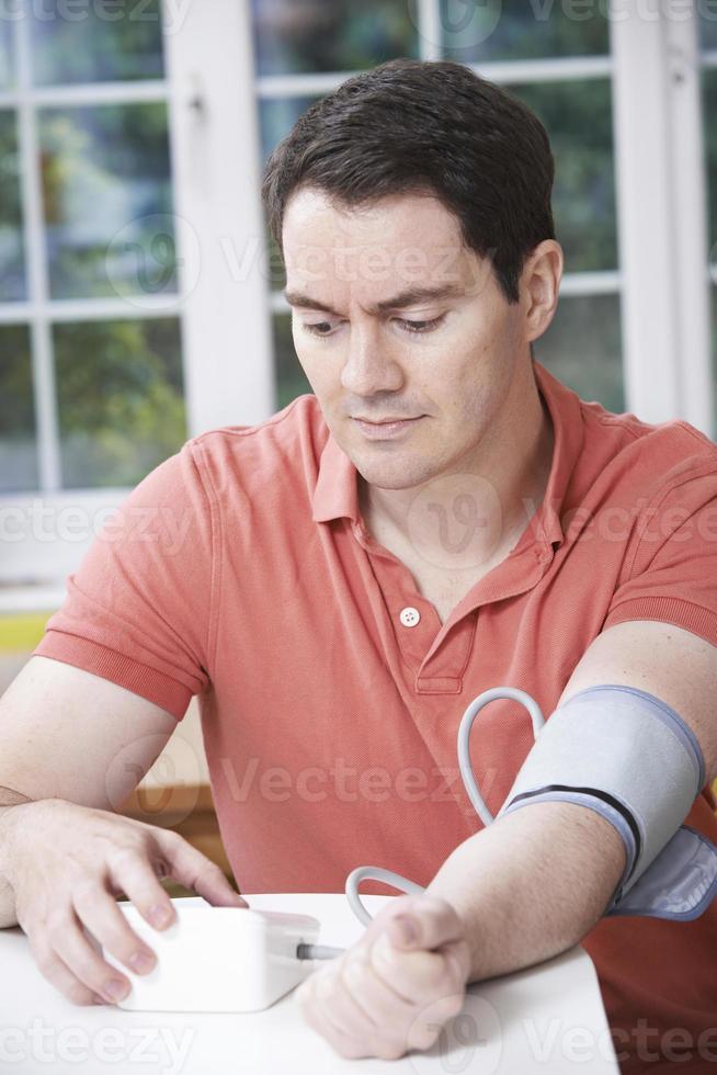 homem medir pressão arterial em casa foto