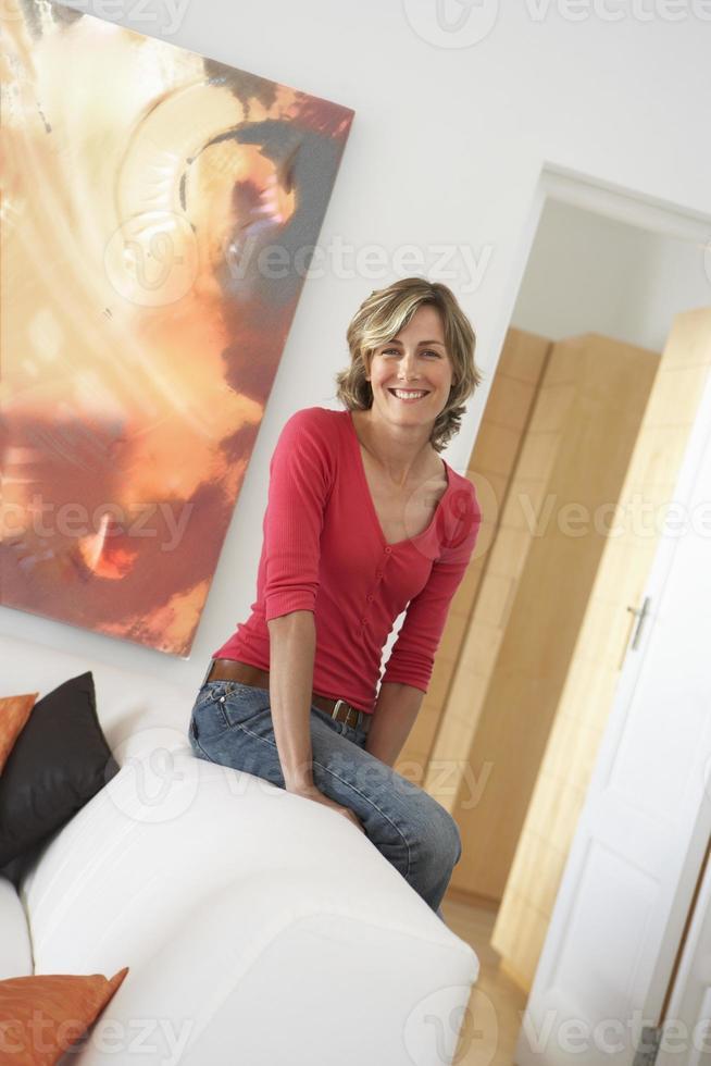 mulher loira, apoiando-se na poltrona em casa foto