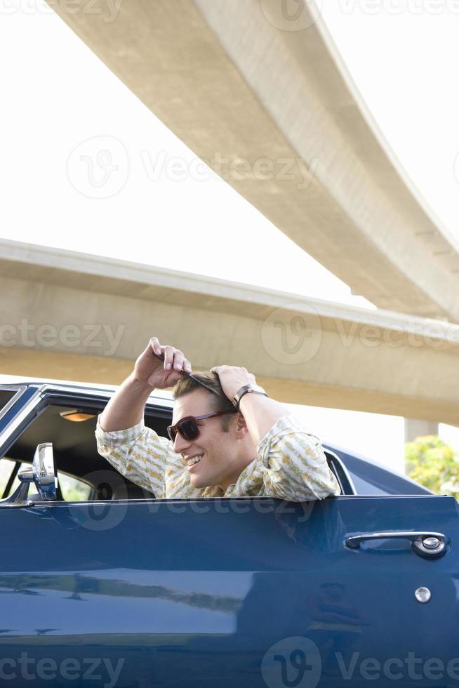 jovem no carro penteando o cabelo no espelho retrovisor foto