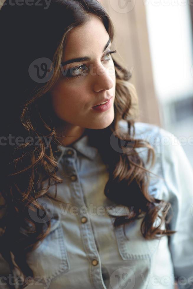 mulher jovem e bonita olhando pela janela foto