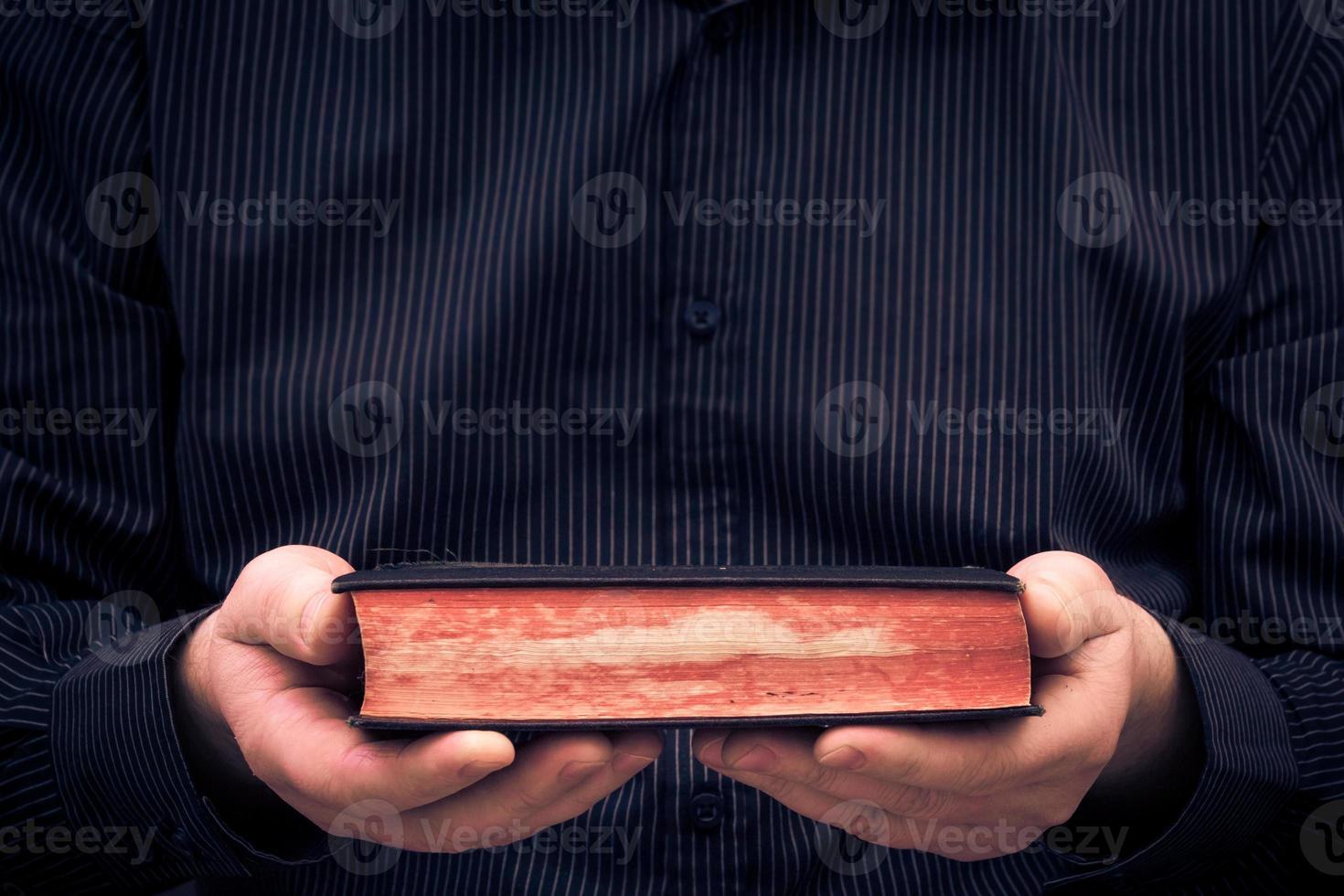homem mantém mãos livro antigo foto