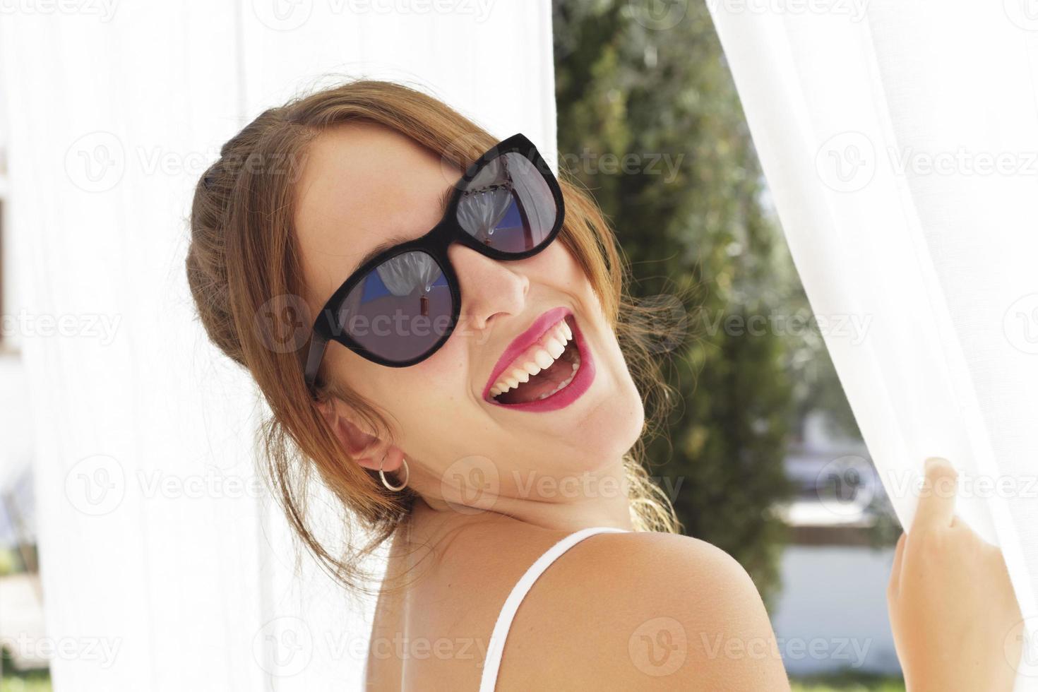 jovem mulher rindo, com óculos de sol, entre cortinas brancas foto