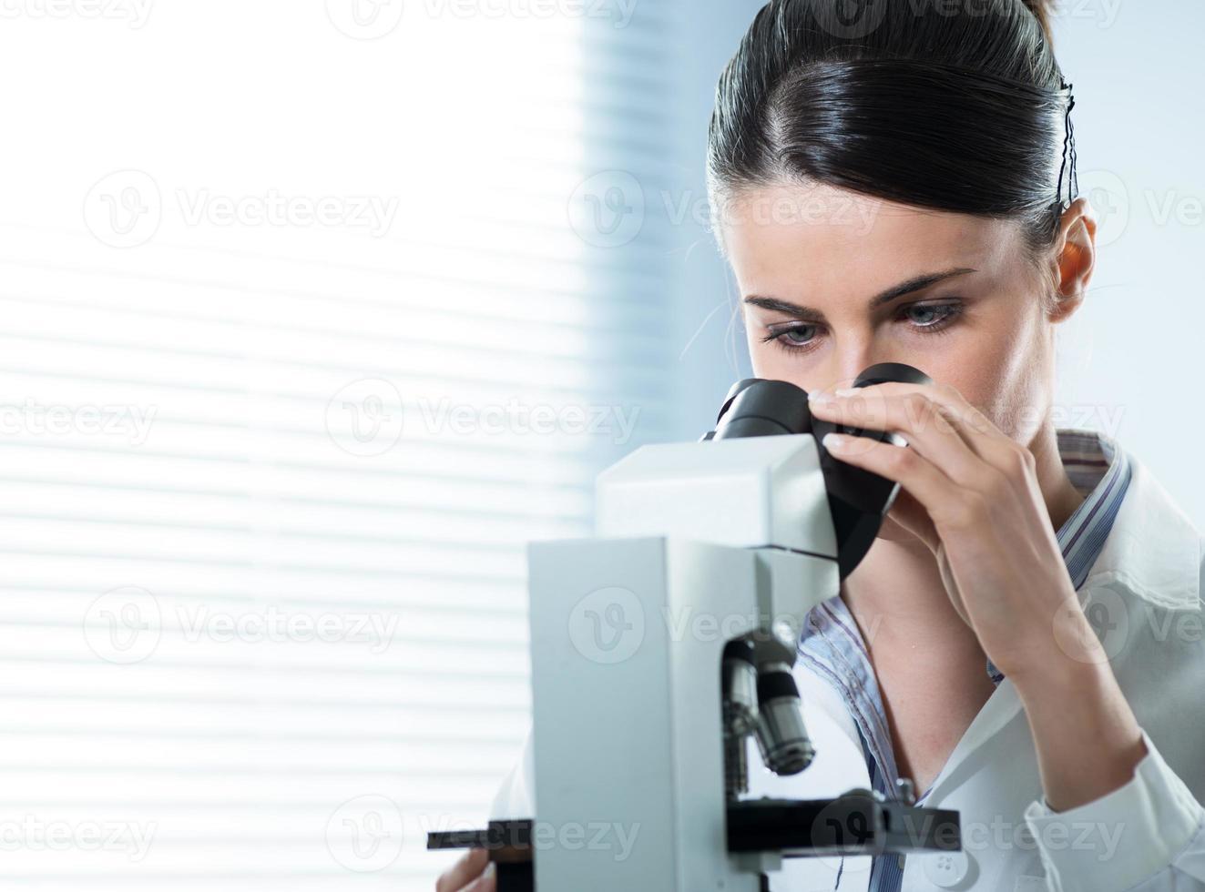 pesquisador feminino usando microscópio close-up foto