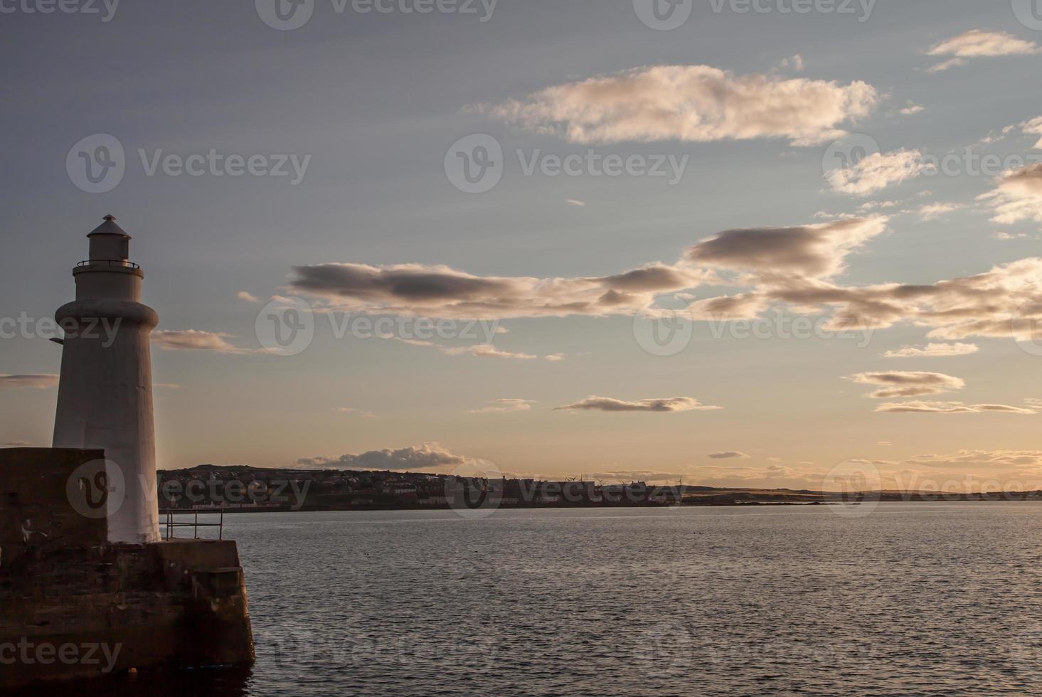 farol e pôr do sol no mar foto