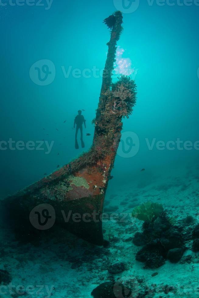 silhueta de mergulhador e um velho naufrágio foto