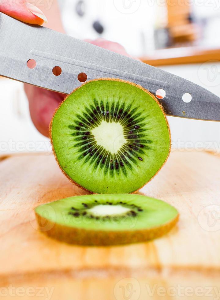 mãos de mulher cortando kiwi foto