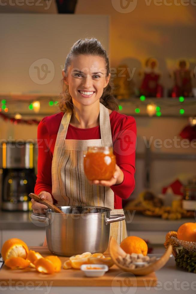 retrato de dona de casa jovem sorridente, mostrando geléia de laranja caseira foto