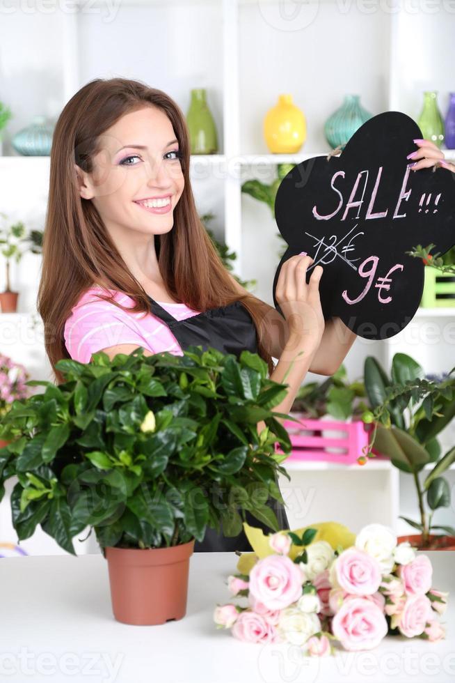 florista de menina bonita na loja de flores foto