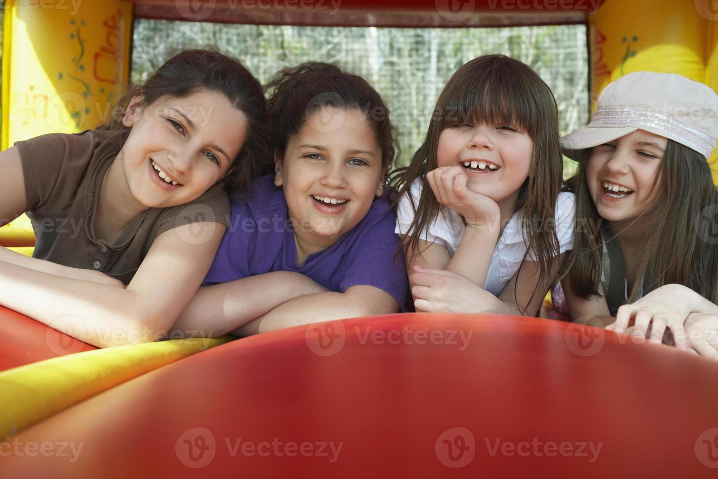 meninas alegres deitado no castelo inflável foto