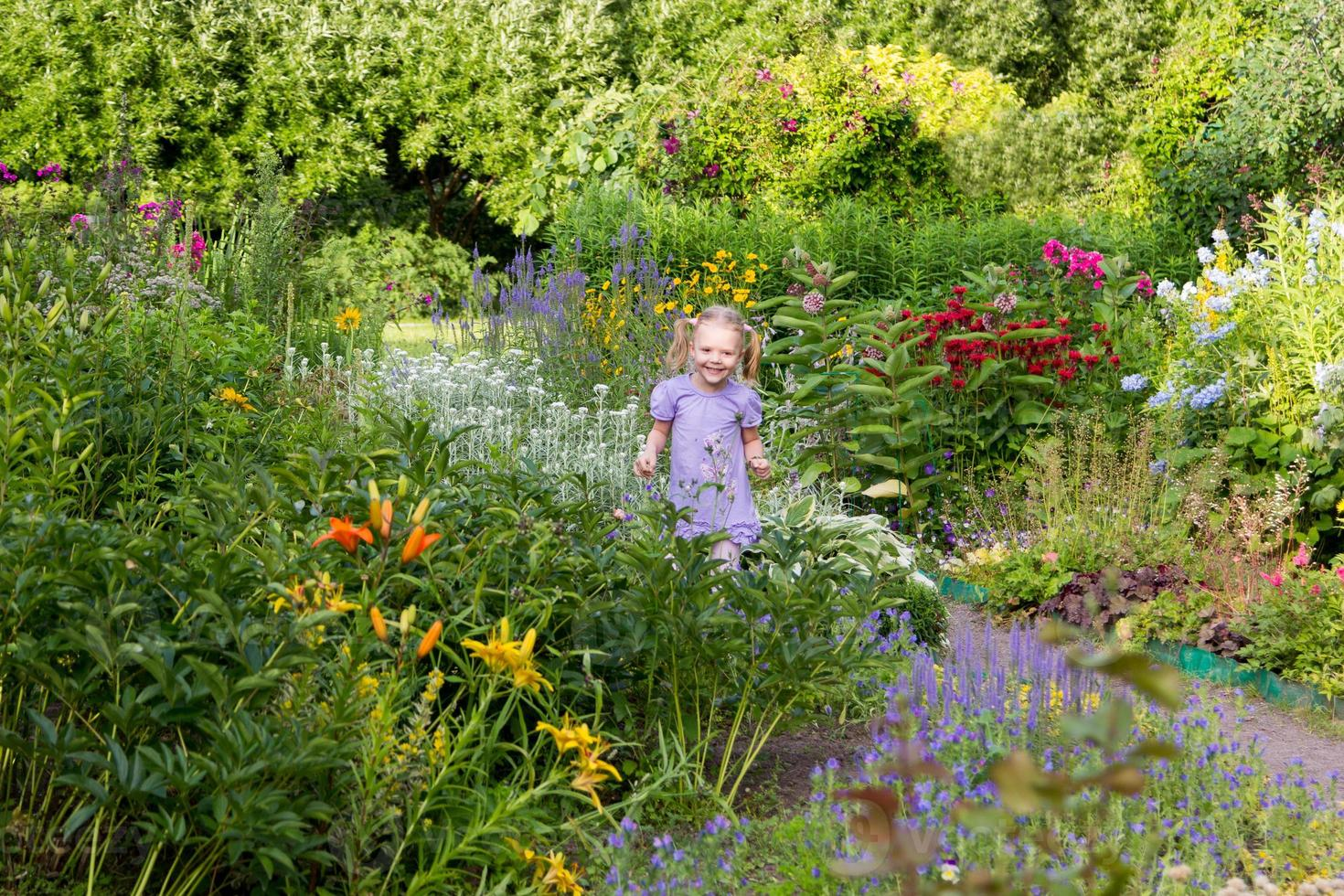 menina alegre entre flores no parque foto