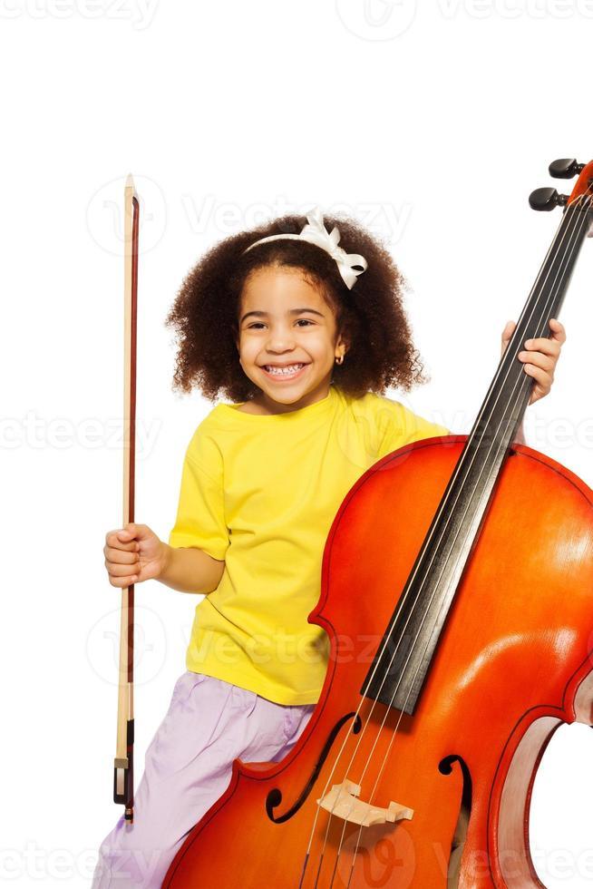 alegre garota africana detém violoncelo com violino foto