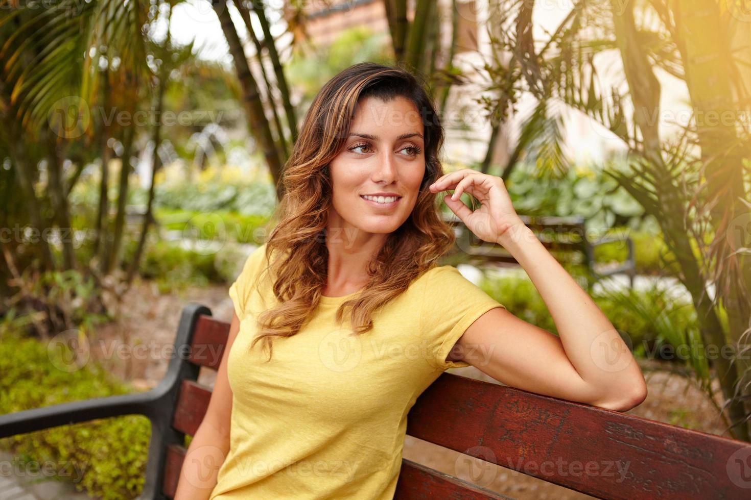 alegre senhora olhando para longe enquanto está sentado no banco foto