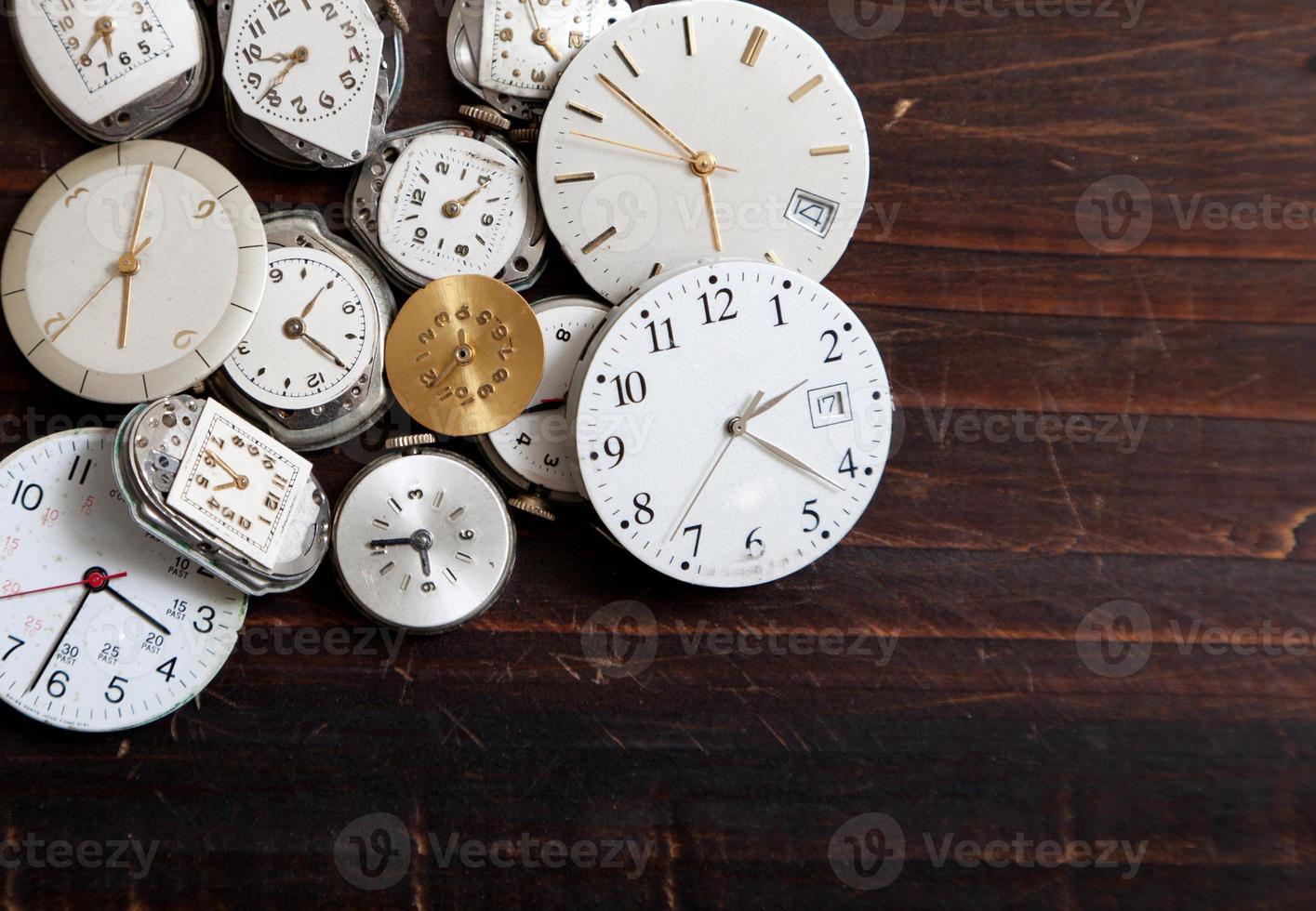 grande variedade de mostradores de relógio de pulso em um fundo de madeira foto