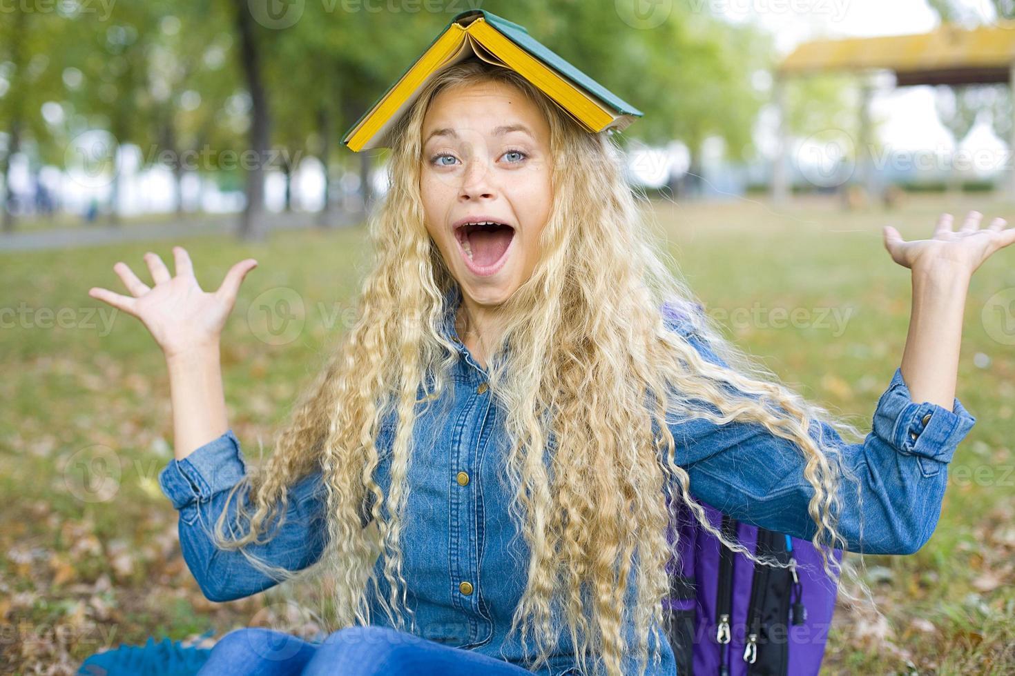 aluna alegre com um livro na cabeça foto