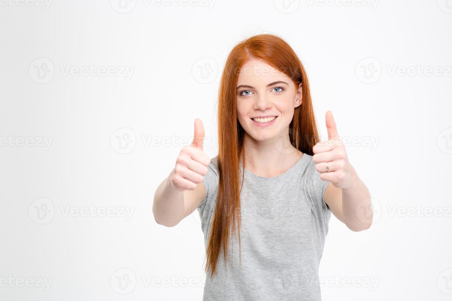 mulher ruiva alegre mostrando os polegares com as duas mãos foto