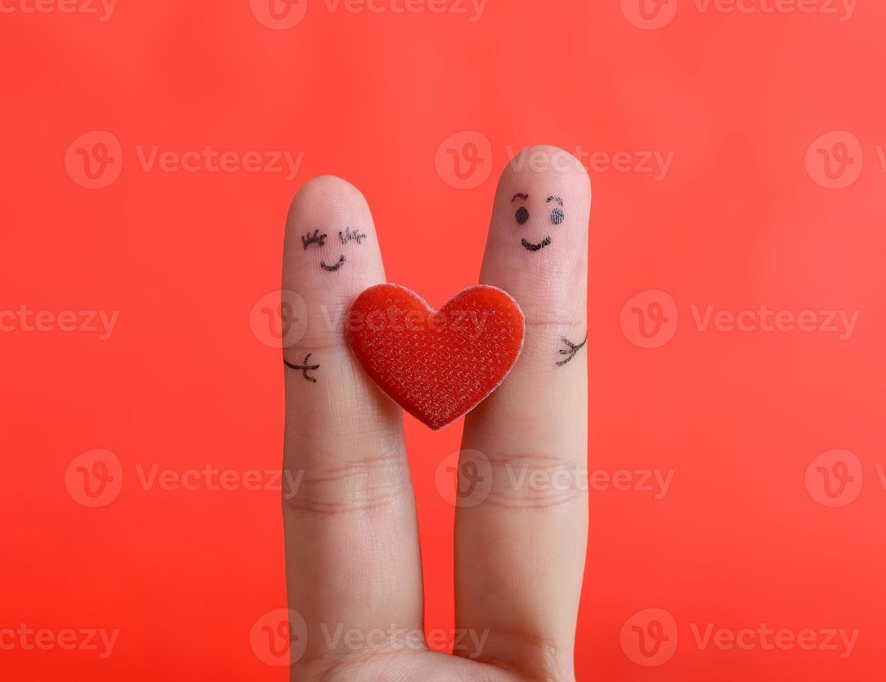 smiley de dedo pintado sobre fundo vermelho, conceito de dia dos namorados. foto