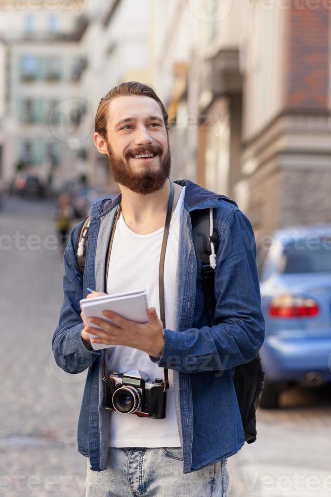 alegre homem barbudo está fazendo sua jornada na cidade foto