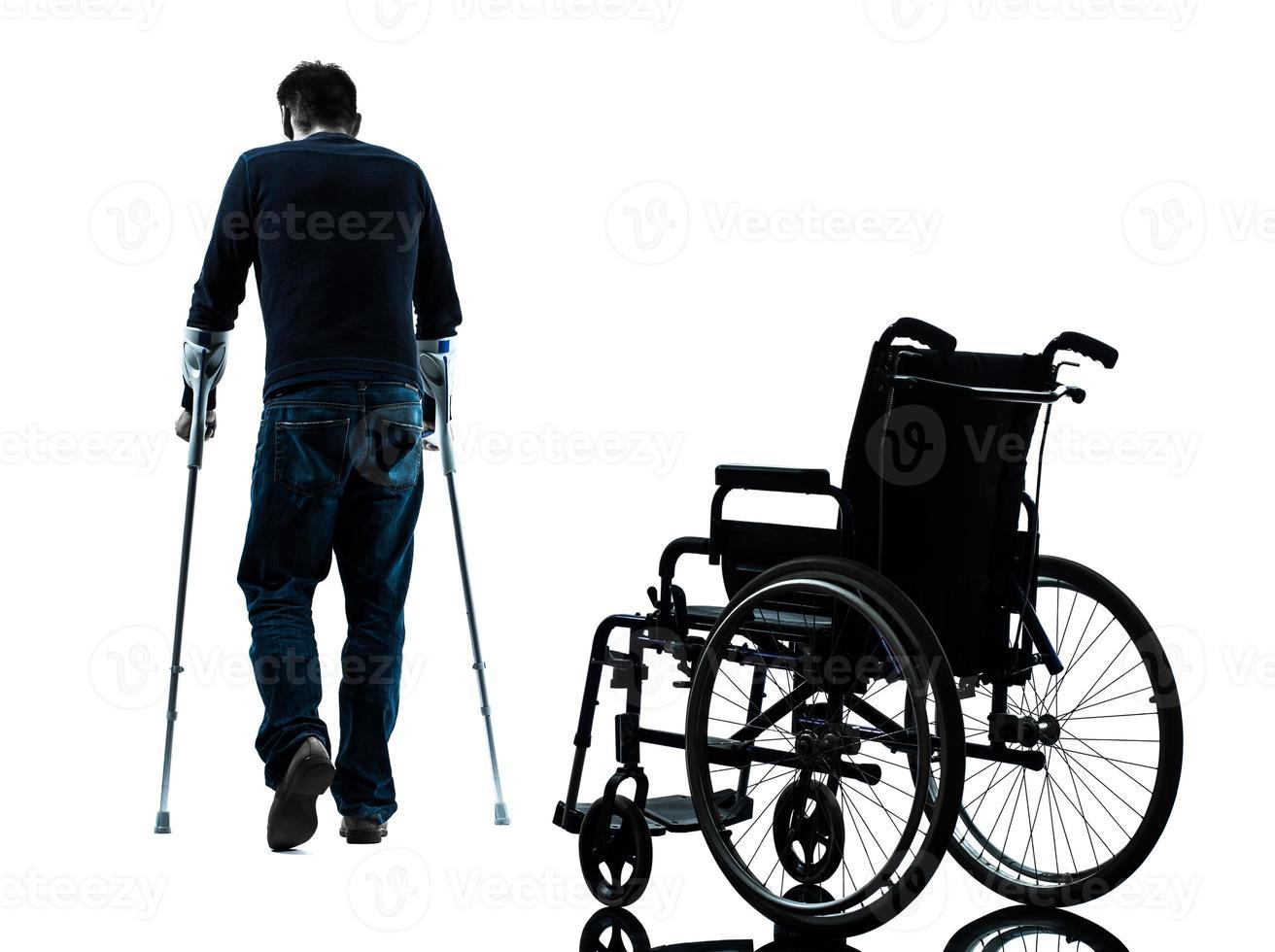 homem ferido com muletas andando longe da silhueta de cadeira de rodas foto