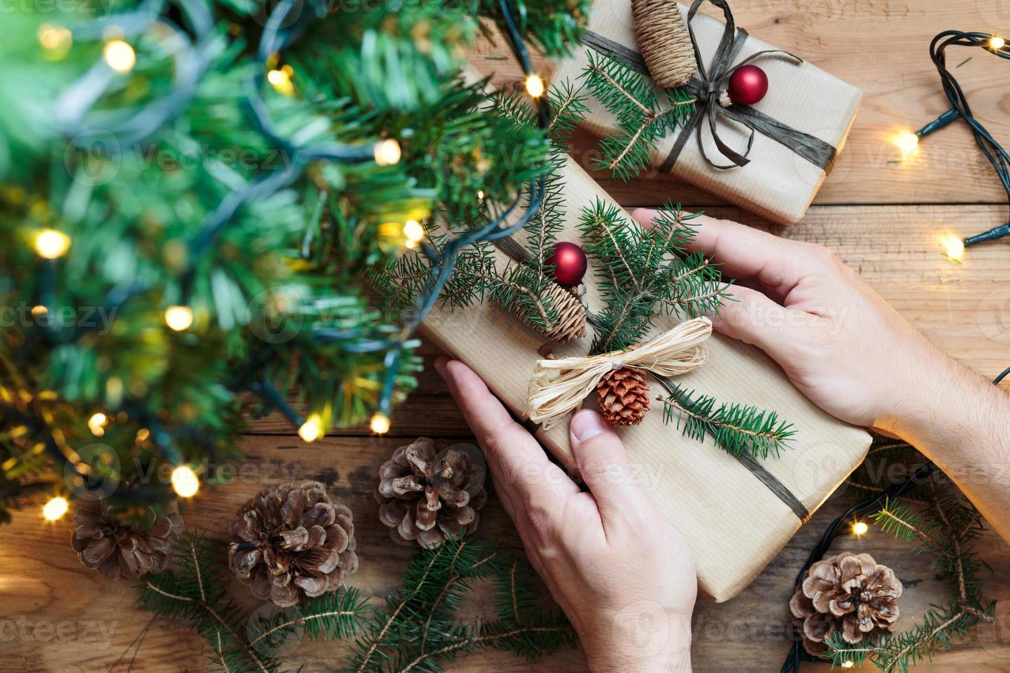 colocando presentes de natal debaixo de uma árvore foto