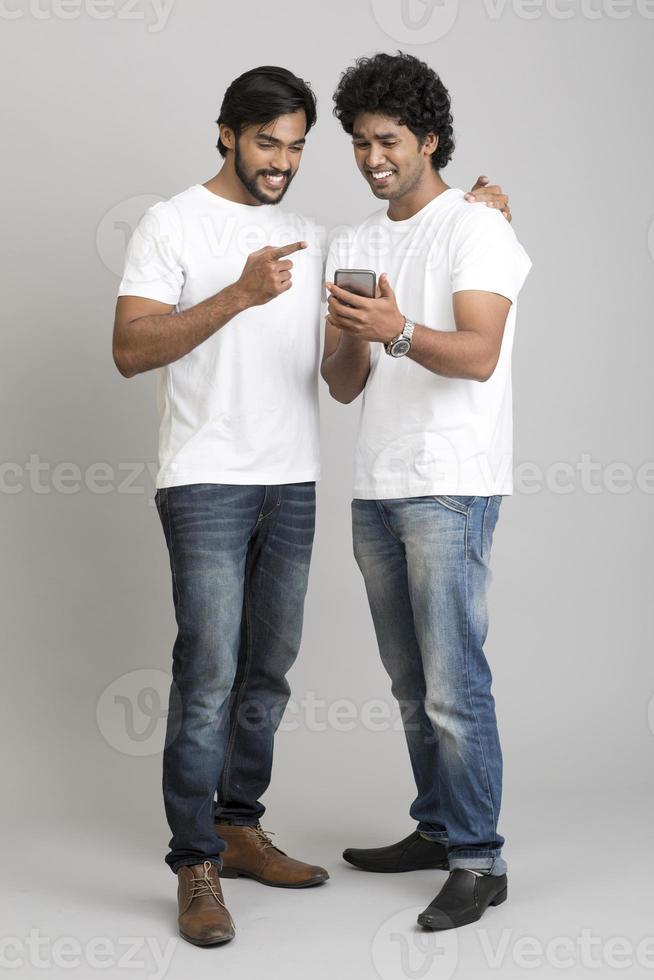 alegres felizes dois jovens usando smartphone foto