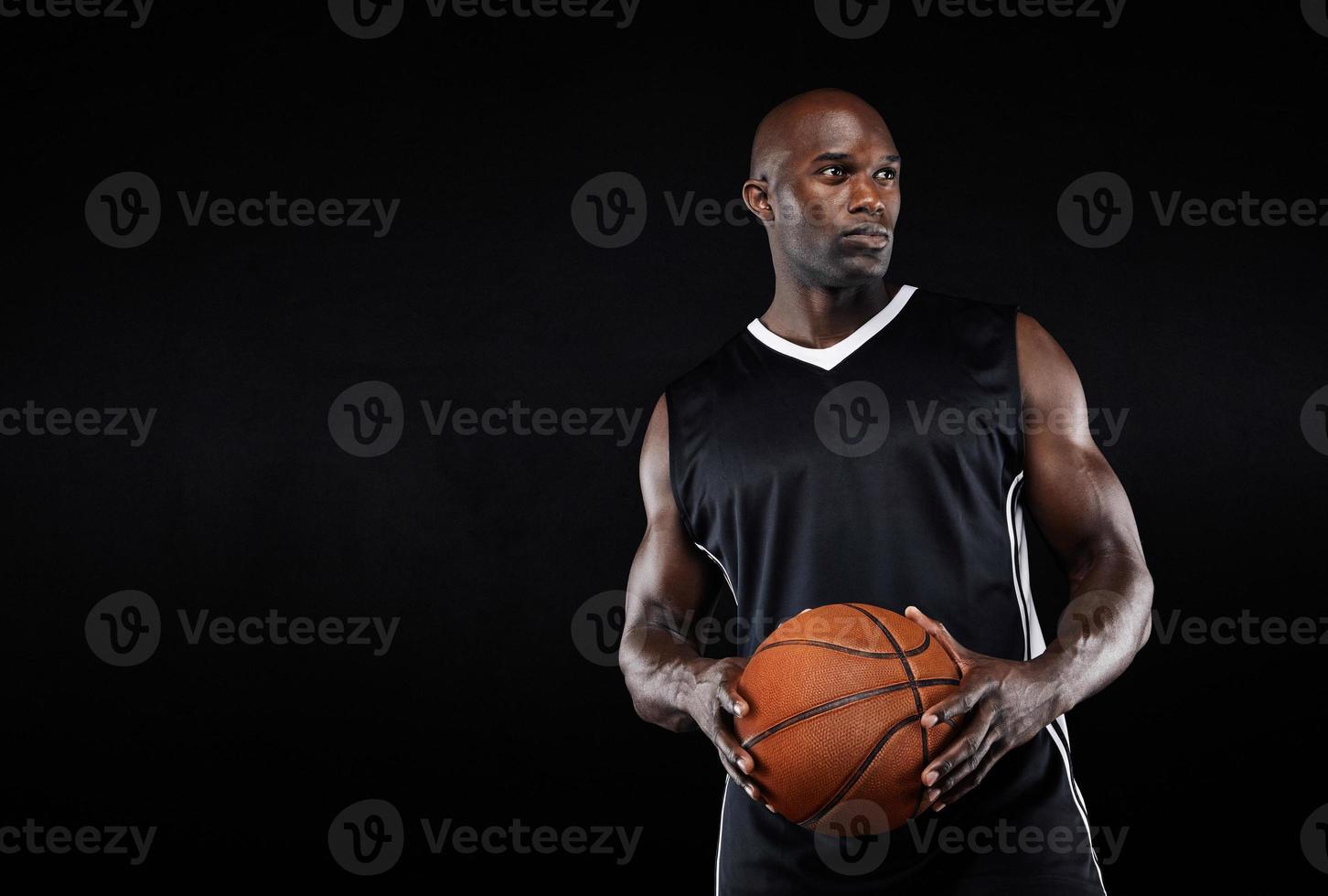 jogador de basquete muscular em fundo preto foto