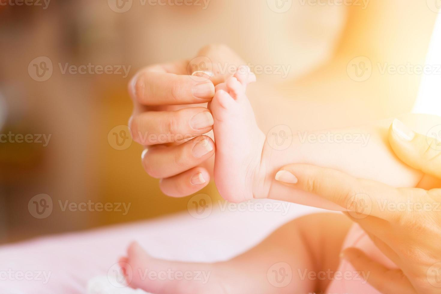 bebê com mãe, ela está segurando os pés foto