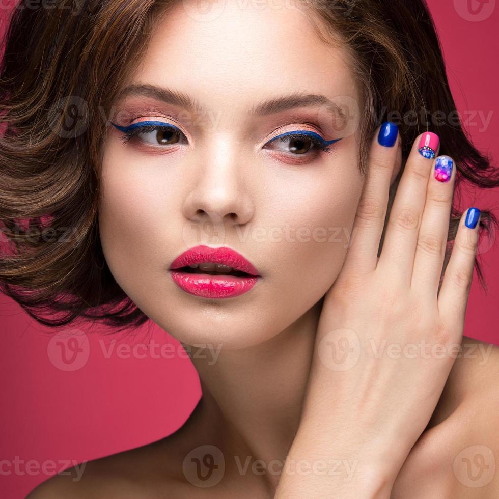 menina linda modelo com maquiagem rosa brilhante e unhas coloridas foto