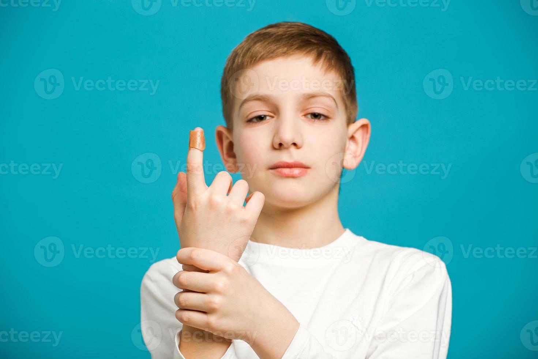 menino infeliz com gesso adesivo no polegar foto