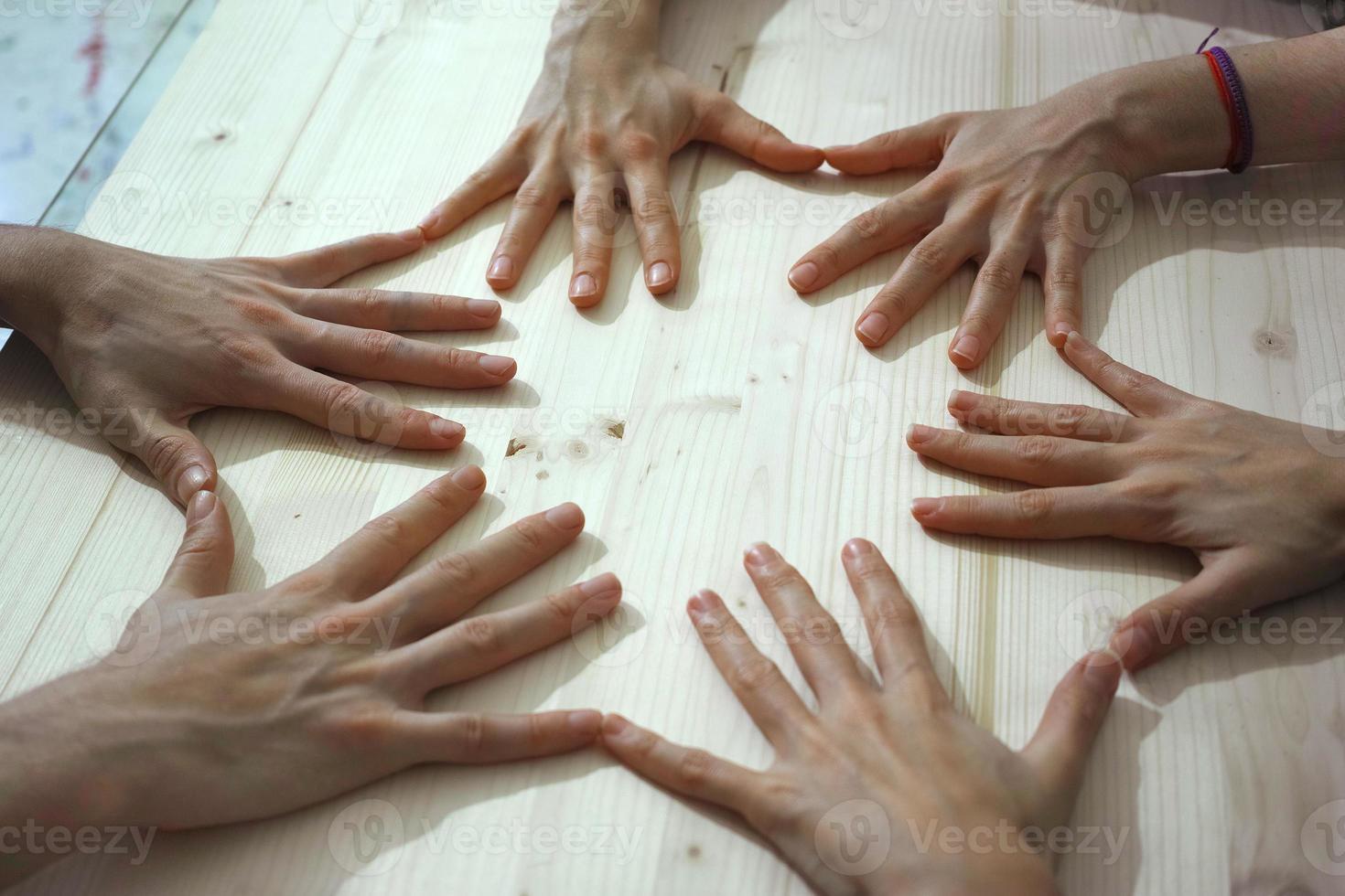 mãos na mesa, fazendo um círculo, tocando as pontas dos dedos foto