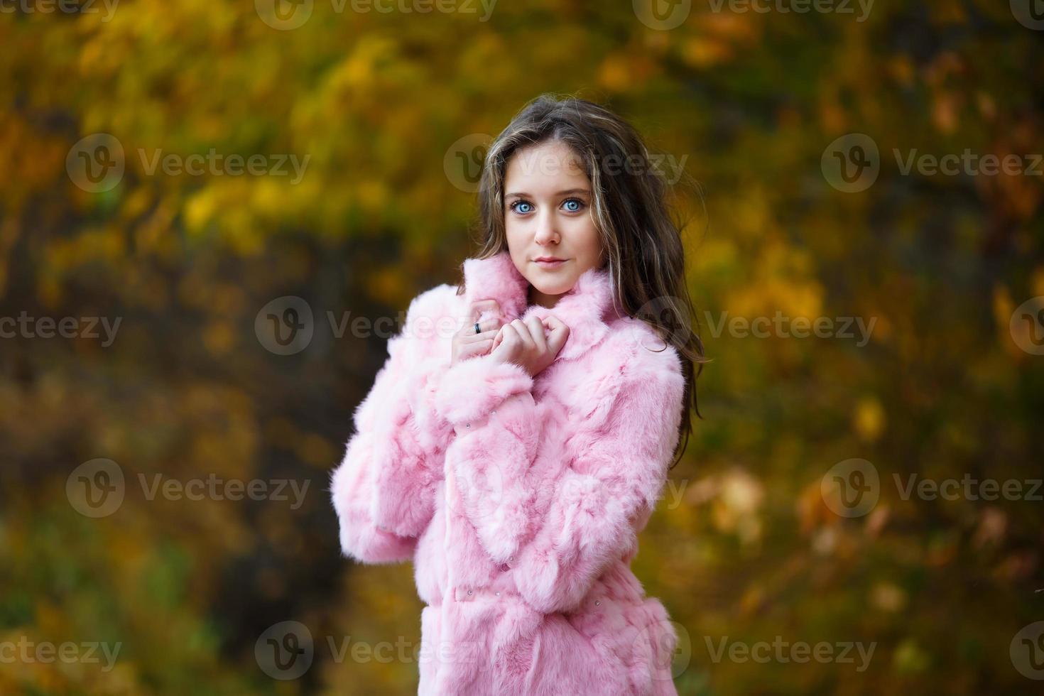 linda garota com um casaco de pele rosa foto