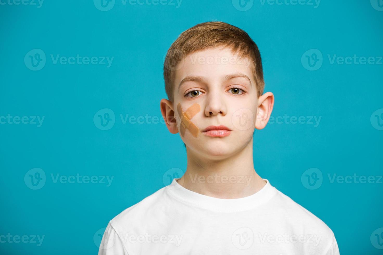 menino com gesso adesivo na bochecha foto