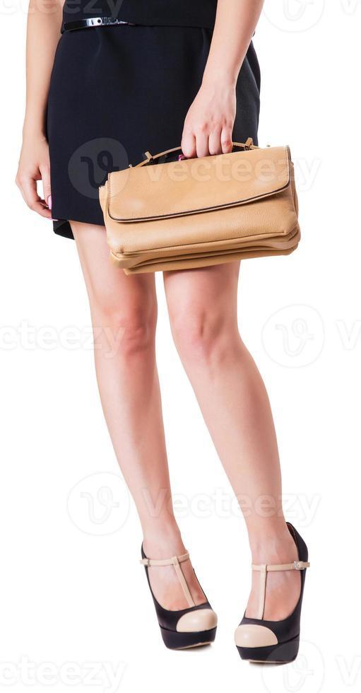 garota de pé com uma pequena bolsa foto