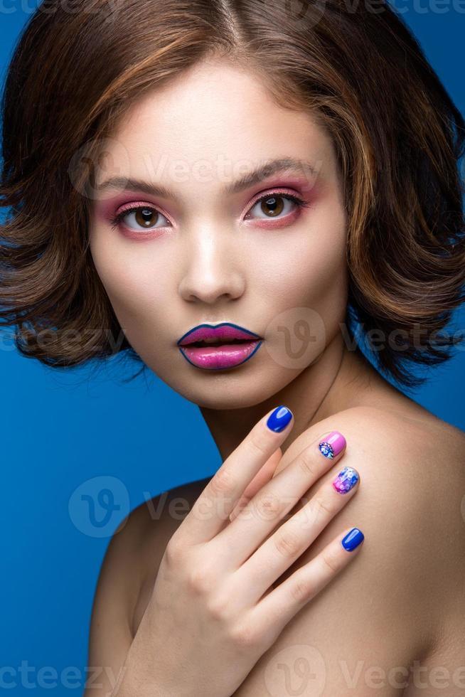 garota linda modelo com maquiagem brilhante e esmaltes coloridos. foto