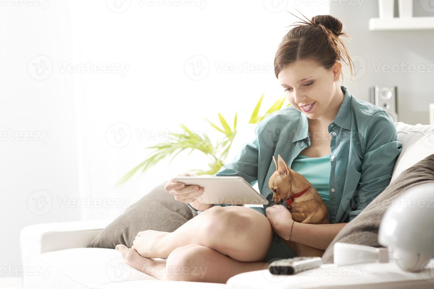 menina com tablet no sofá foto