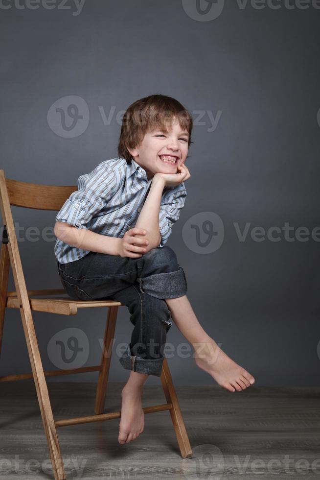 retrato de menino feliz, alegria, sobre um fundo cinza foto
