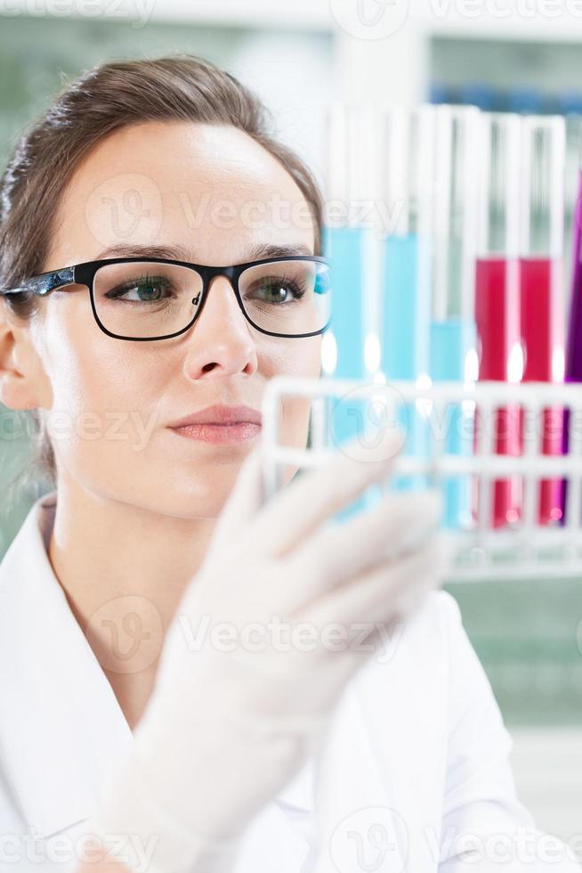 químico olhando para tubos de ensaio foto
