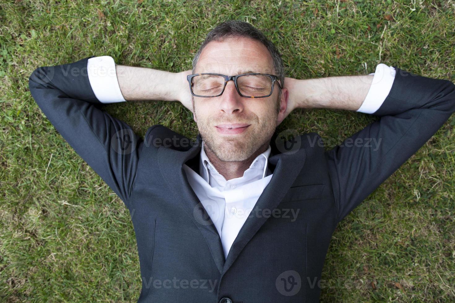 empresário relaxado emocionado, deitado na grama ao ar livre foto