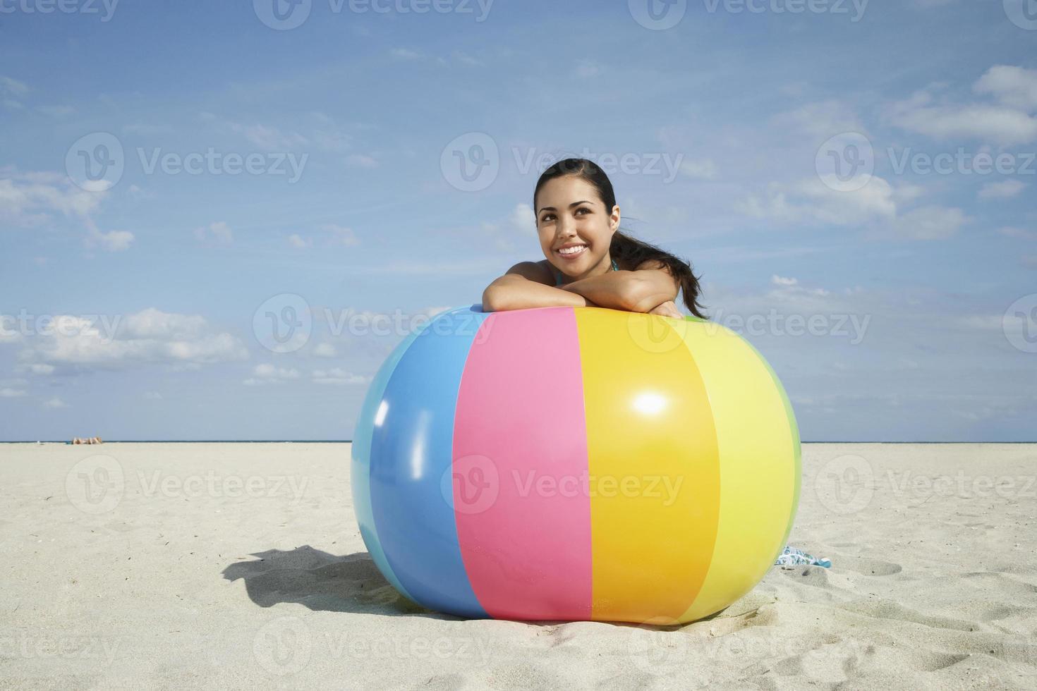adolescente relaxante na bola de praia colorida foto