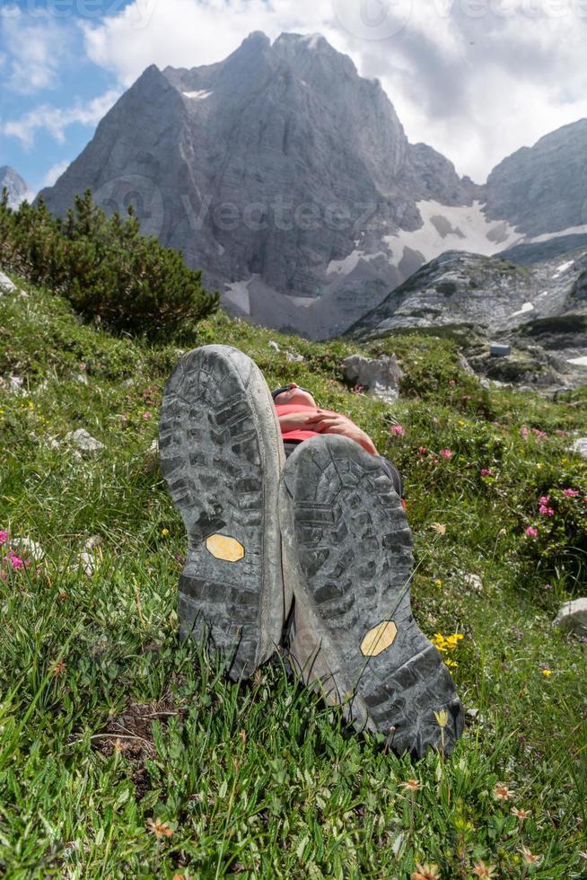 jovem relaxante em um prado de montanha foto