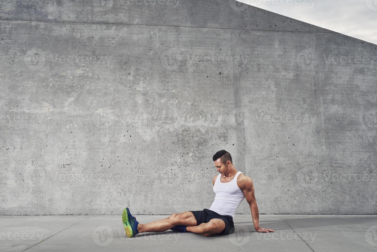 homem de atleta fitness relaxando e esticando os músculos e pernas foto