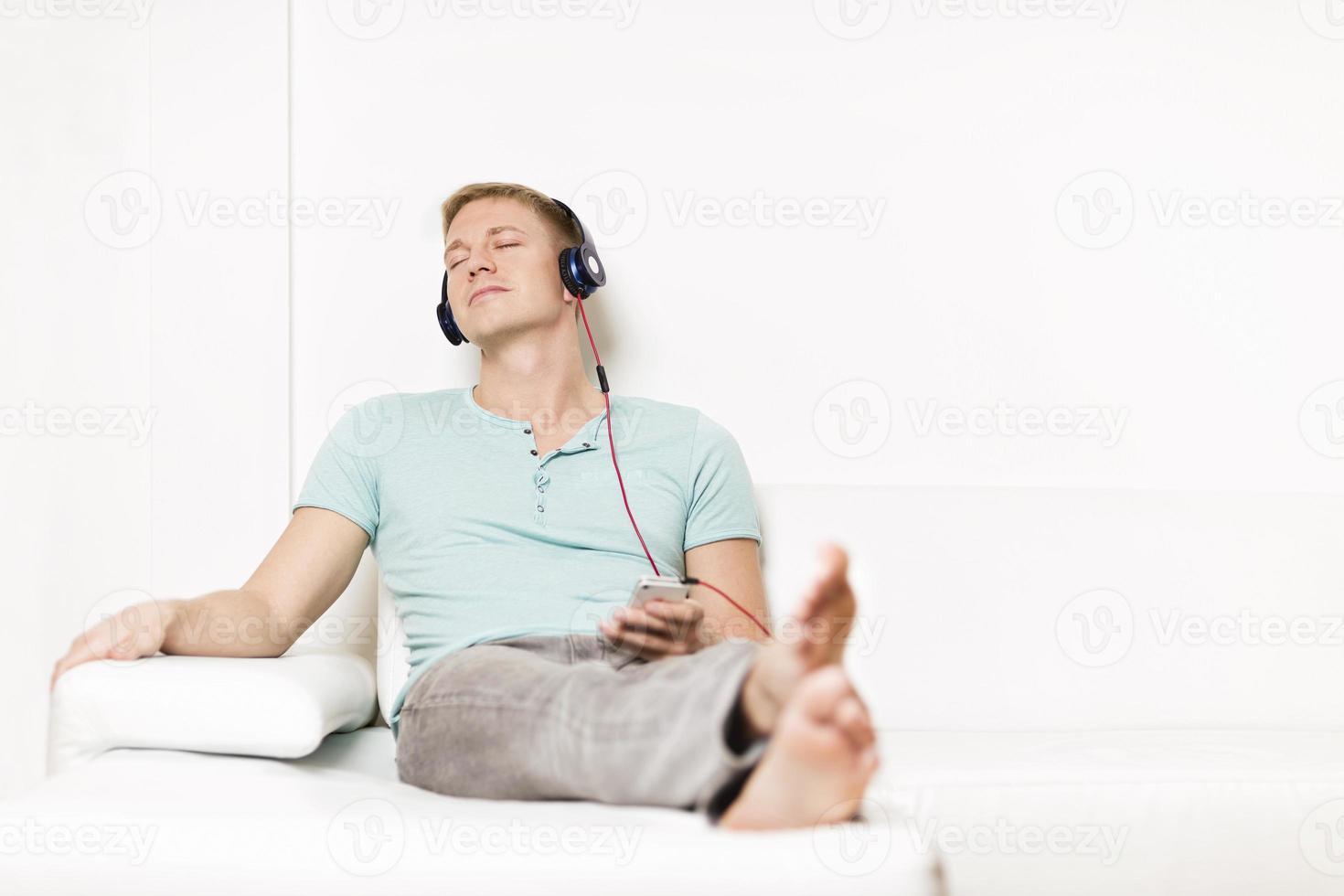 homem relaxado ouvindo música com fones de ouvido e olhos fechados. foto