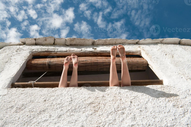 duas garotas relaxam com as pernas fora da janela rústica foto