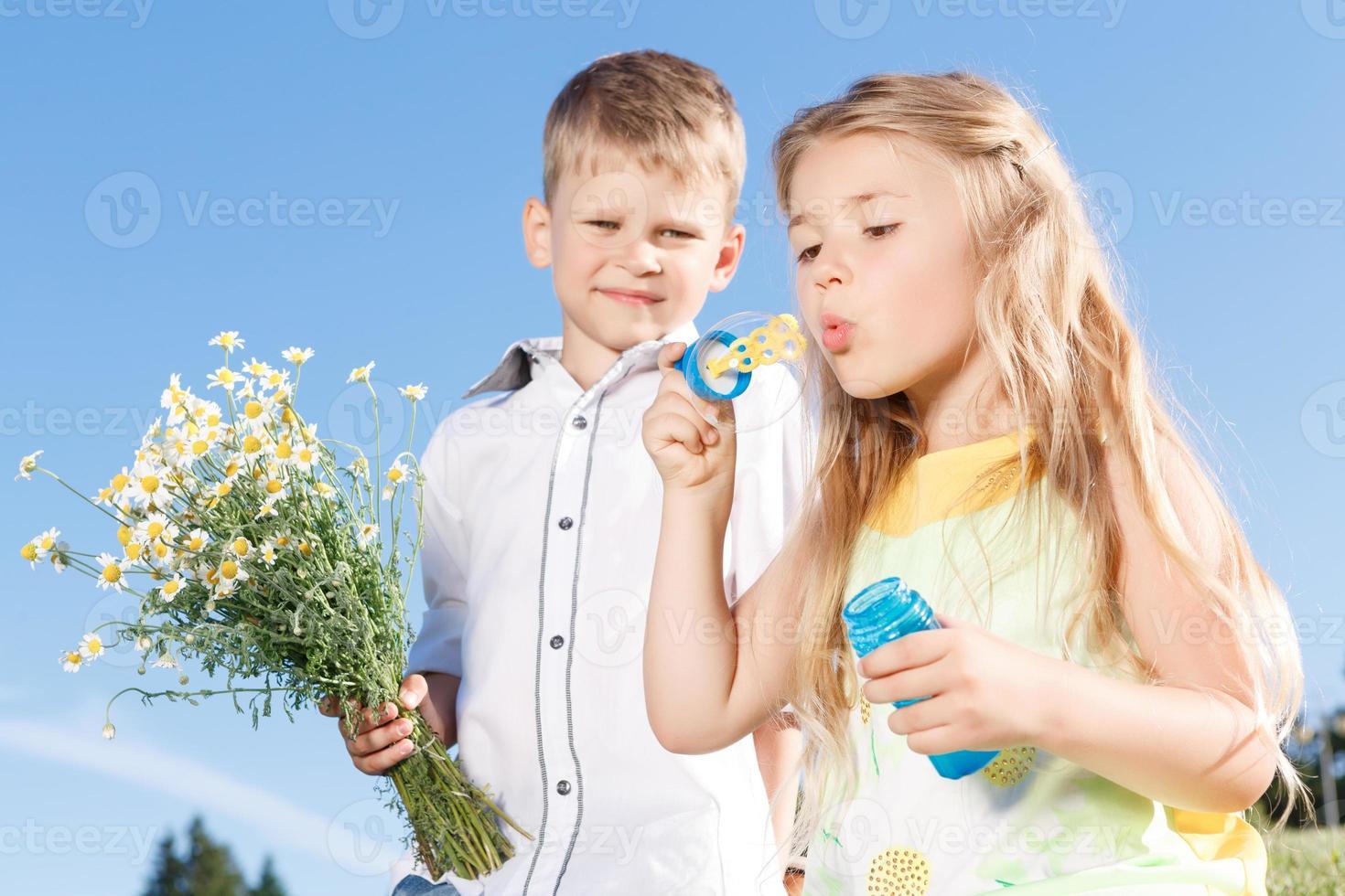 crianças positivas soprando bolhas de sopa foto