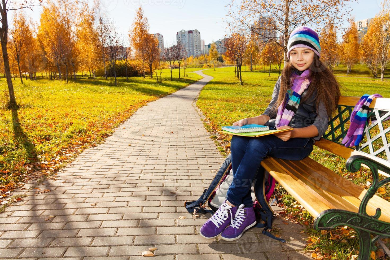 menina da escola com livros didáticos no parque foto