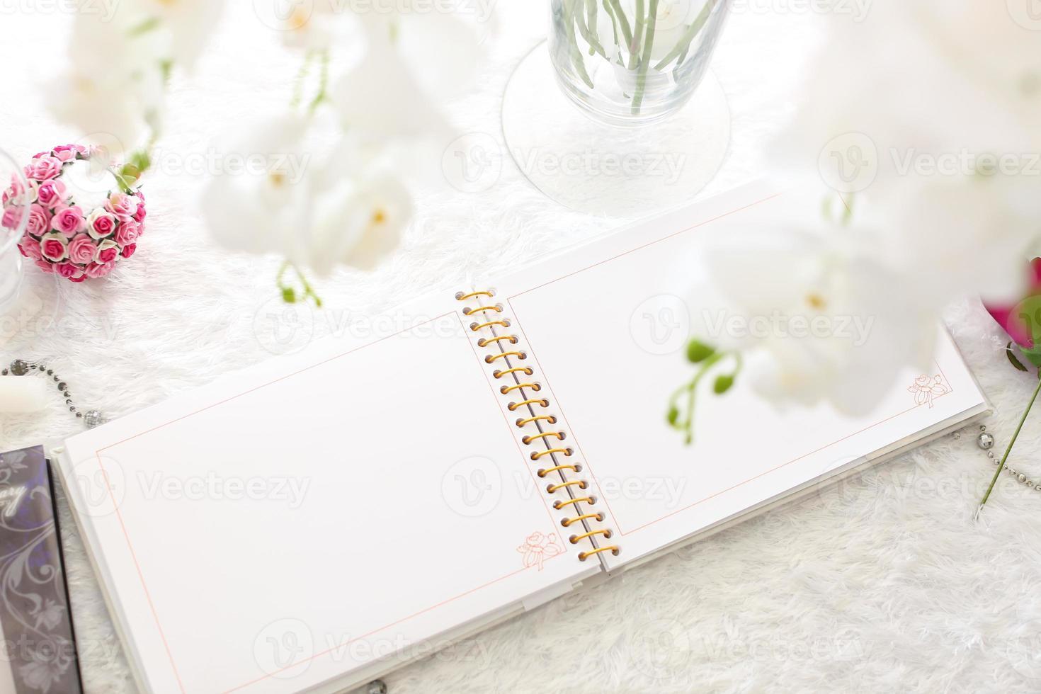 caderno em branco em uma mesa de madeira branca foto