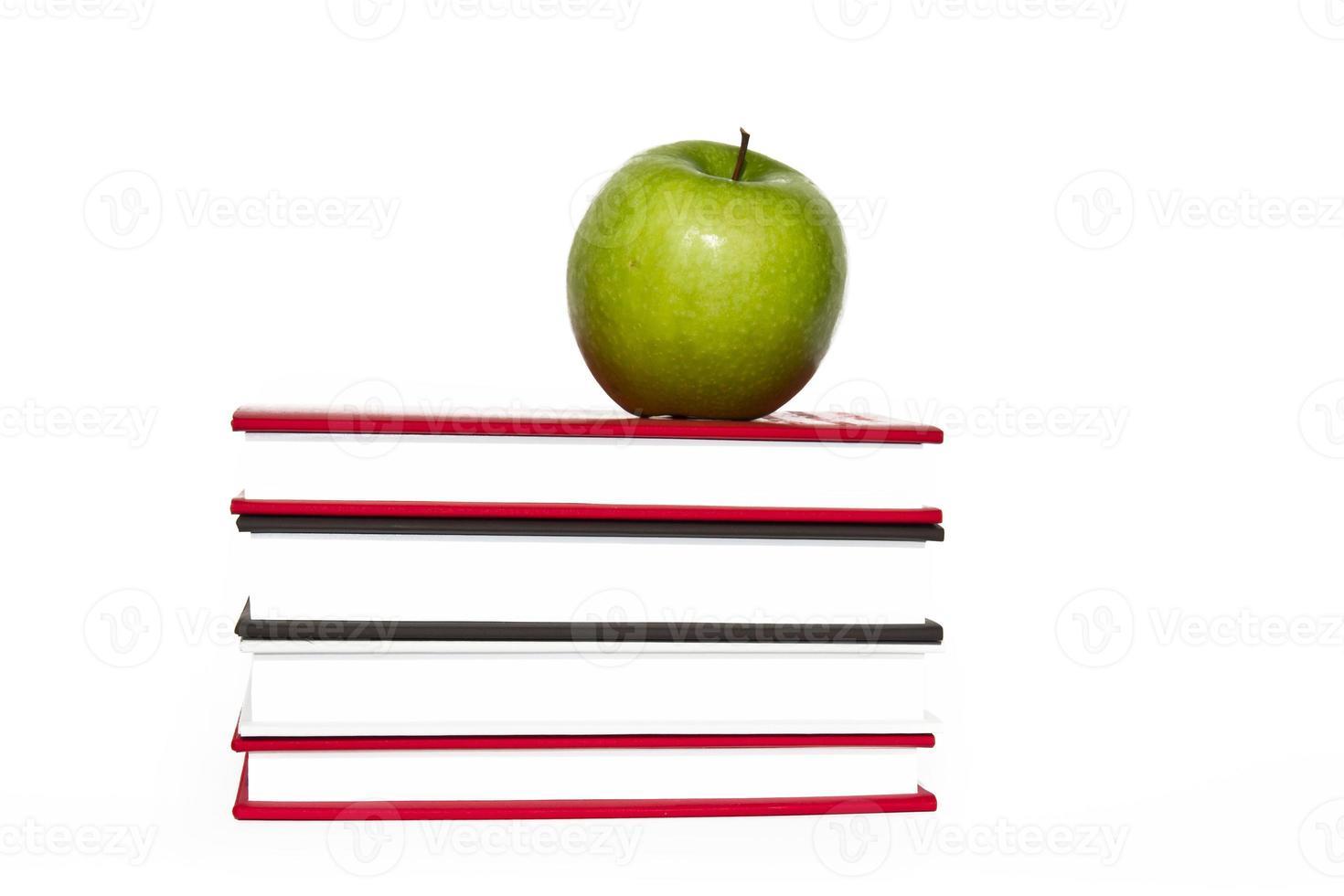livros e maçã isolado no fundo branco foto