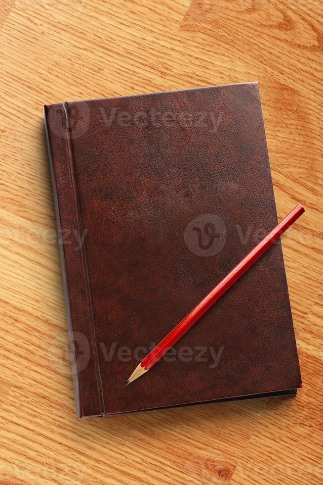 caderno em branco escuro com lápis vermelho foto