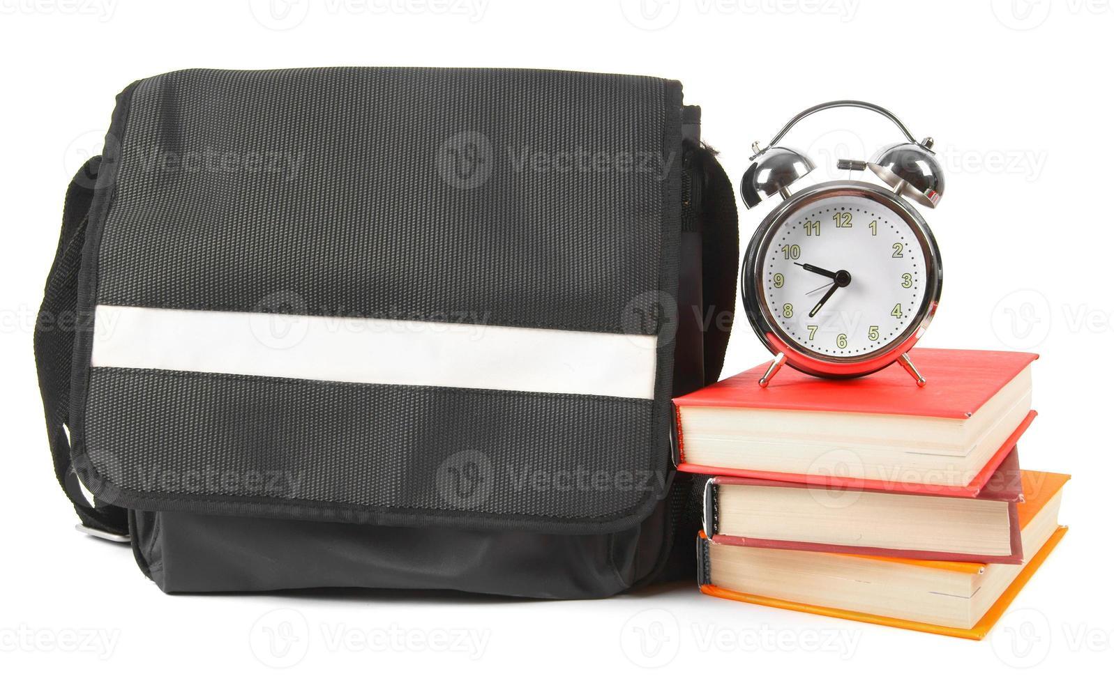 mochila escolar, livros e despertador. foto