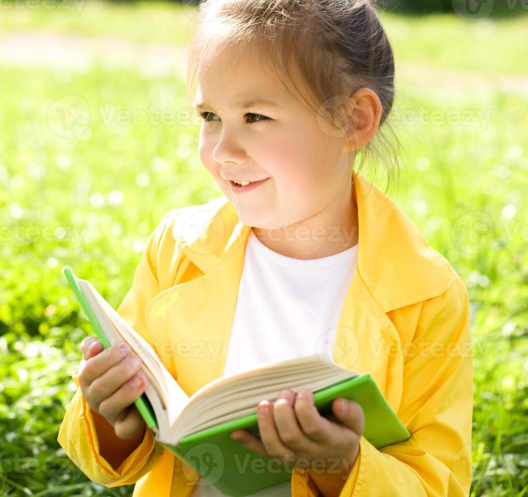 menina está lendo um livro ao ar livre foto